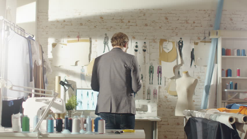Male Fashion Designer Pins Clothing Sketches to the Wall. His Studio is Sunny, Personal Computer Shows His Work.Colorful Fabrics,Clothes Hanging and Sewing Items are Visible.Shot on RED EPIC 4K (UHD).