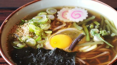 Japanese soba noodle hot soup with green onion, naruto, seaweed and raw egg