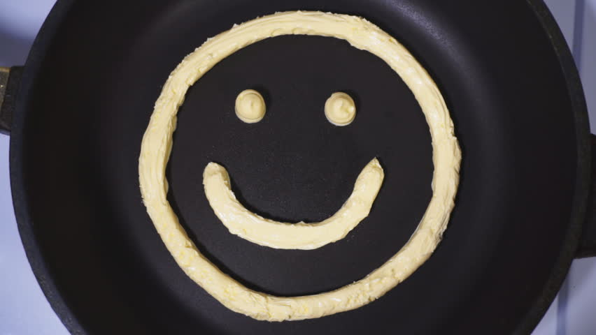 Smiley face made from butter, accelerated video. Butter being heated and melts in a skillet