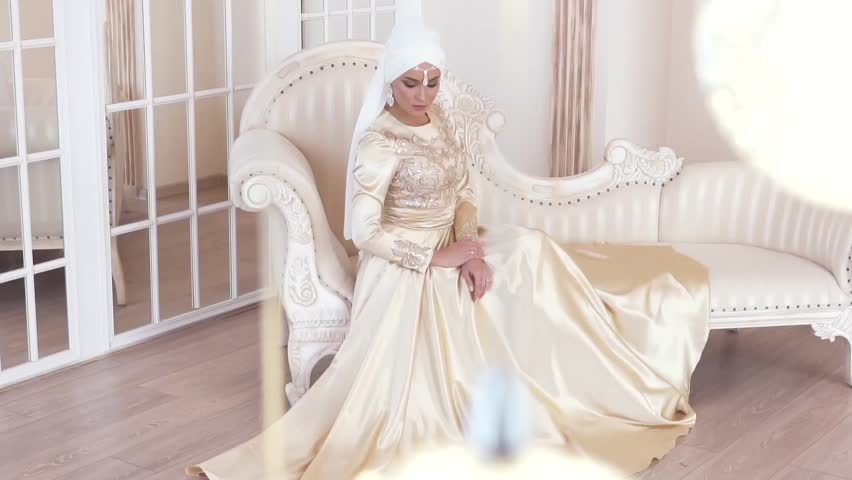 138aa00a Portrait of a beautiful muslim bride in gold wedding dress with Beautiful  white headdress sitting on sofa in studio with tablet, slow motion
