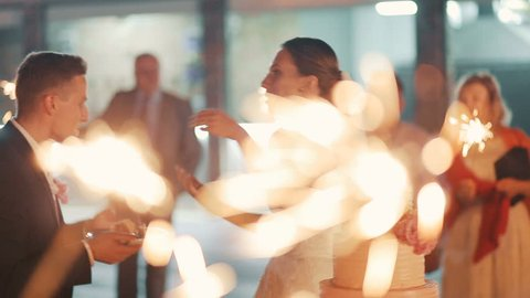 Beautiful young wedding couple eating cake, guests with sparklers