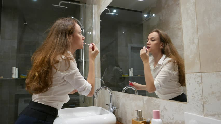 Young adult woman put on red liquid lipstick, make morning preparation at apartment bathroom. Lady bend to large mirror, carefully rouge lips, look to reflection. Office worker get ready to go out