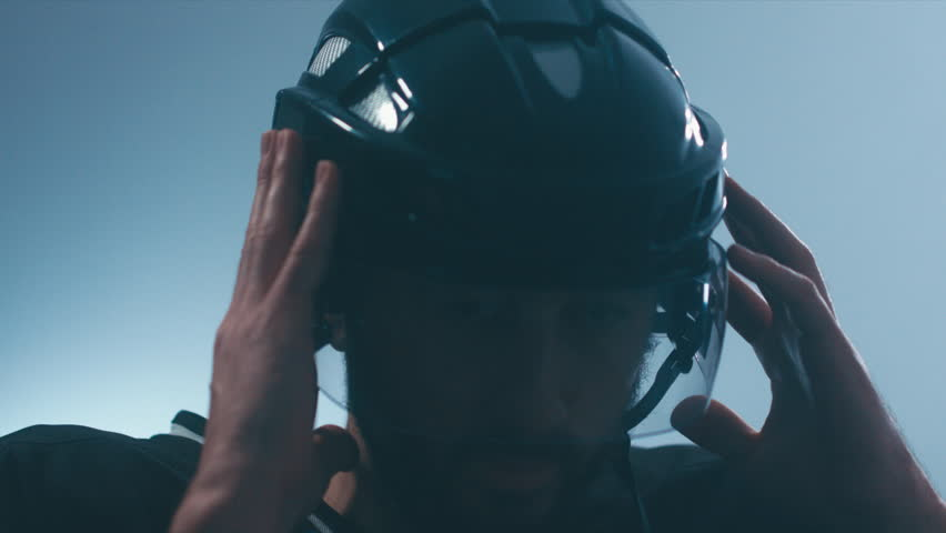 CU Portrait of Caucasian male ice hockey player in black uniform putting on his protective helmet in locker room, turning into camera. 4K UHD 60 FPS slow motion. RAW edited footage | Shutterstock HD Video #23567443