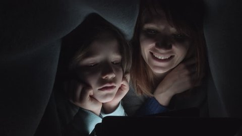 4k Shot of Child and Mom Looking on Tablet under Blanket