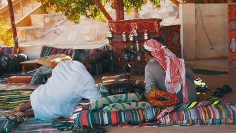 EGYPT, SOUTH SINAI, SHARM EL SHEIKH, DECEMBER 1, 2016: Bedouins and Arabs are drinking tea at table in Egypt. The Arabs have a rest in a cafe near the sea. men dressed in traditional clothes are