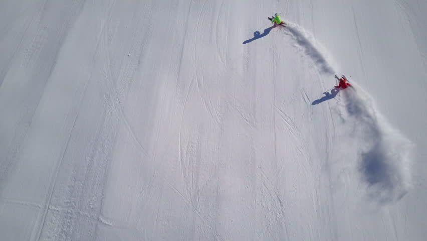 4k footage, top aerial drone view two skiers skiing on empty ski slope in clouds of snow