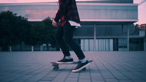 Fashionable rider in hipster red plaid shirt and black jeans just skates on his longboard at twilight time with beautiful paster lightning, camera follows him