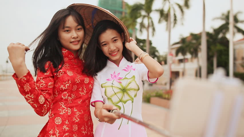 Two beautiful Vietnamese girl doing selfie with phone in national dresses Ao Dai