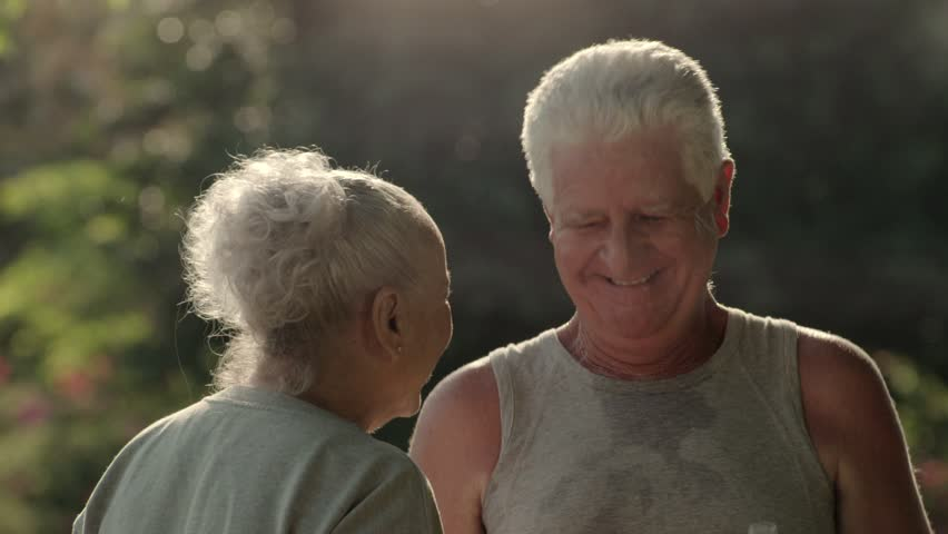 Active senior people and sports, old man and woman talking and drinking water after exercising in park