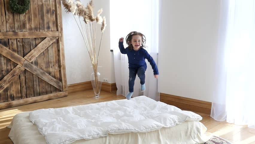 Carefree Childhood - Cute Little Happy Child Girl Enjoy Jumping Lying And Rolling On A White Bed At Home