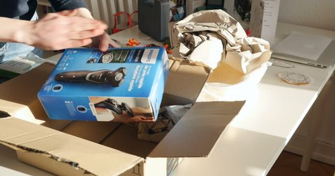 PARIS, FRANCE - CIRCA 2017: Fast motion time lapse woman unpacking unboxing a cardboard from Amazon.com with a Philips Philishave electric shaver - delivered box by courier object bought online