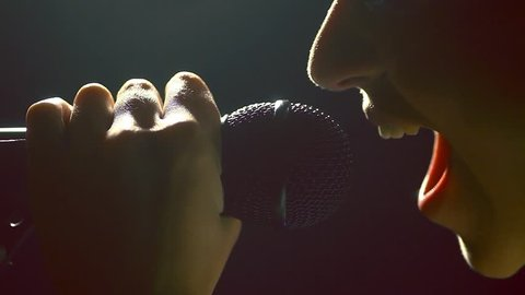 Close up footage of a woman screaming to a microphone.