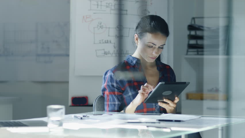 Female Design Engineer Sits at the Glass Table in Her Office, Works on a Tablet Computer, Blueprints Laying on Her Desk. In the Background Whiteboard with Diagrams and Sketches.