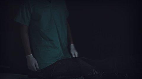 4K Crime Morgue. Mortician Opens Black Bag with Dead Body