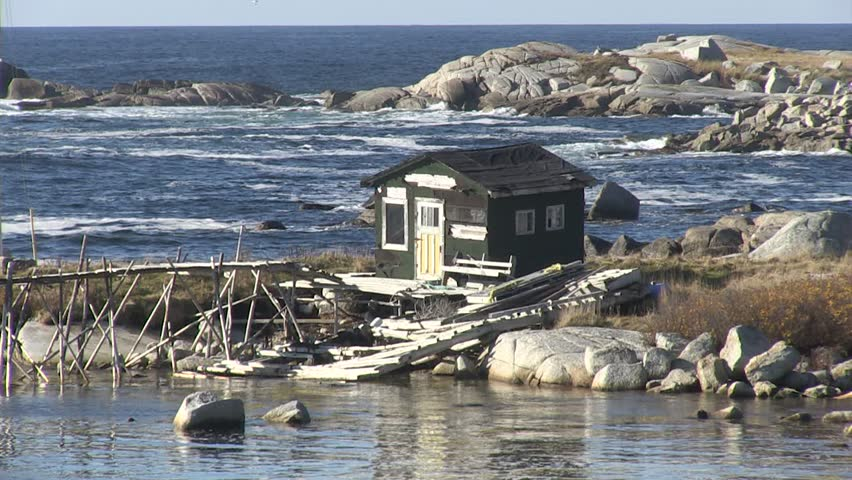 Fishing shack on the Atlantic Ocean.  The sunny day doesn't make the cold ocean look any more inviting.  Lots of waves breaking in the background, this dilapidated shack has seen better days.