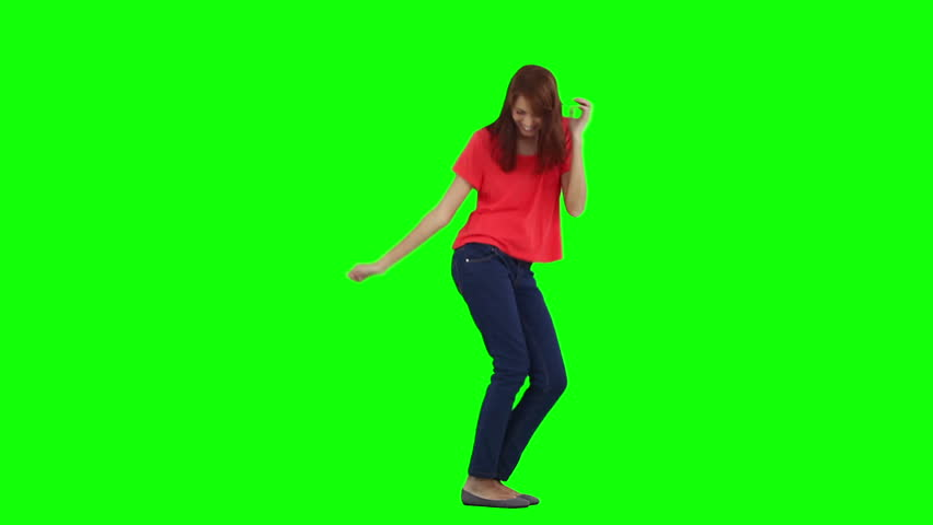 A happy woman is dancing on her own against a green background