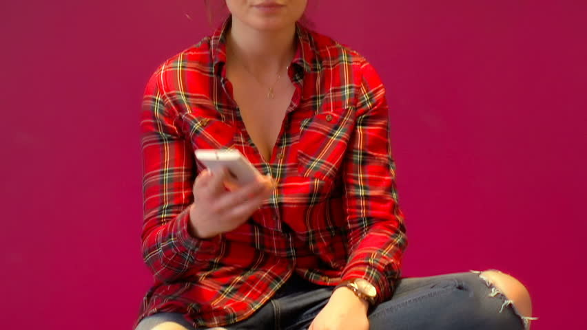 Girl in red, checked shirt answers cellphone and looks worried, steadycam shot  | Shutterstock HD Video #23717683