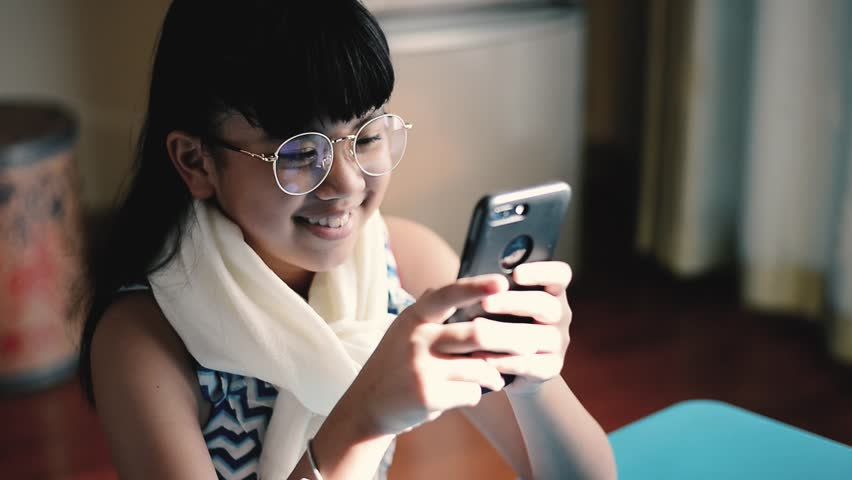 Girl using mobile phone , young attractive girl using  smart phone and texting on mobile phone  in home, Smart phone   | Shutterstock HD Video #23739883