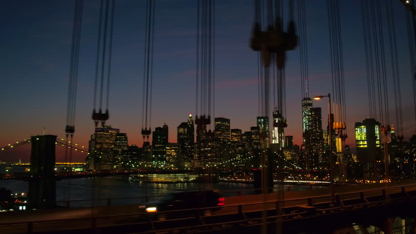 Driving over famous Manhattan Bridge overlooking iconic Brooklyn Bridge and modern glassy skyscrapers and highrise buildings illuminated with city lights in downtown business district at night | Shutterstock HD Video #23769853