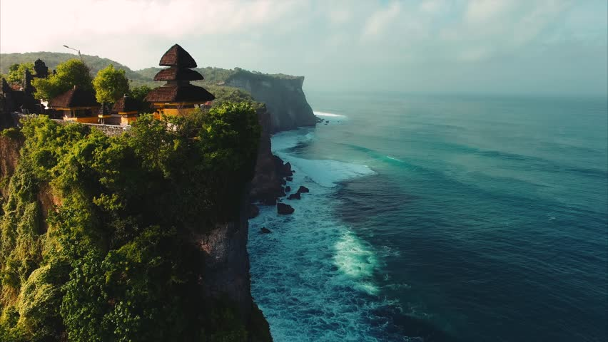 Pura Uluwatu temple. Stone cliffs, ocean waves and oceanscape. Aerial top view. Bali, Indonesia.