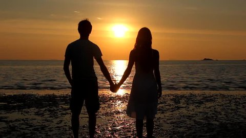 Couple silhouette staring at sunset on the beach start kissing and she lifts one leg up bending her knee in Koh Phangan island, Thailand. Valentine Day, honeymoon romantic love celebration concept