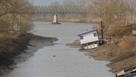 Low water in maas with houseboat in mud. Because of accident in Grave where a weir dam was damaged, the level of the Maas river around Cuijk was very low. Causing problems to houseboats and ferries.