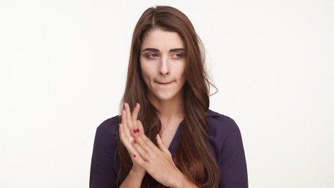 Nervous beautiful Caucasian female with long brown hair wearing dark blue shirt standing kicking her heels rubing hands biting nails on white background