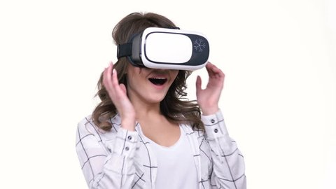 Attractive young woman wearing virtual reality glasses isolated over white