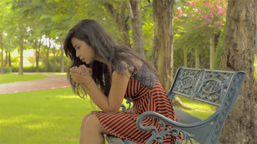 A young Asian woman sitting on a park bench, praying earnestly.