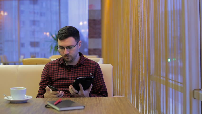 Adult man with smartphone and tablet during breakfast in cafe | Shutterstock HD Video #23838913