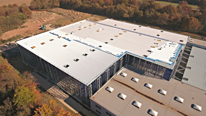 Flying around a new build warehouse building in bird's eye view 4K. Drone jaw shot of building in focus with flat roof. Positioned in middle of forest. Orange forest.