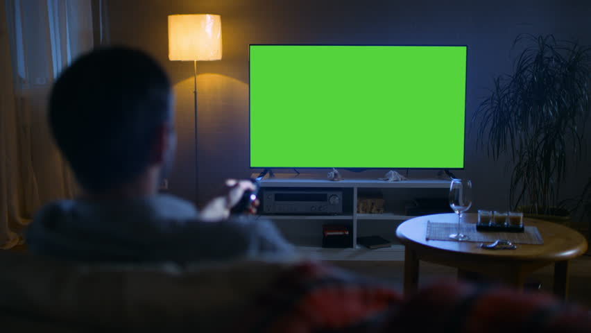 In the Evening Back View of a Middle Aged Man Sitting on a Couch Watching Big Flat Screen TV, He Switches Channels with Remote Control. It's Evening,  Shot on RED EPIC-W 8K Helium Cinema Camera.