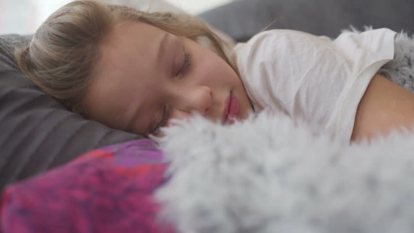 dd8e2dedbfb7 Cute little girl sleeping in bed hugging teddy bear waking up and smiling
