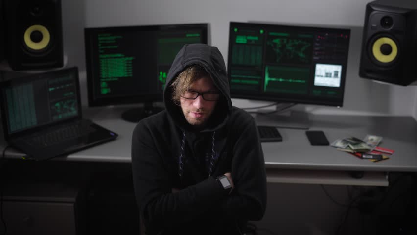 Hacker thinks about how his hack program and then abruptly turns to the monitor screen and starts working. He is wearing a black hoodie, hood hides his head, but some bangs falls on the hair.
