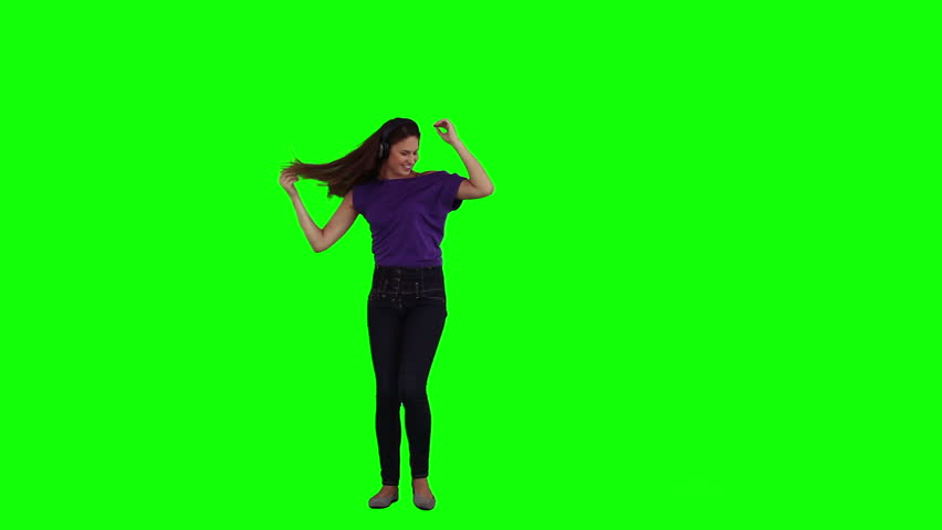 A dancing woman is listening to music on her headphones against a green background