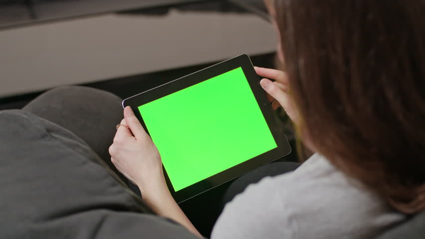Young girl using digital tablet pc with blue screen sitting at home. reading | Shutterstock HD Video #23961373