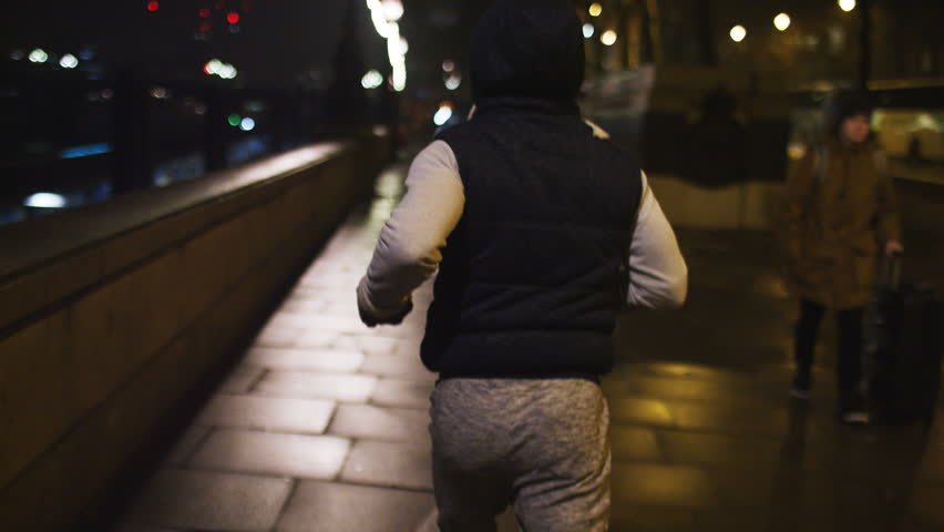 4K Male hooded jogger runs through the city at night