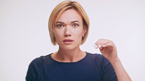 Middle-aged Caucasian female in blue sweatshirt and blonde hair looking at camera in disgust gesturing on white background in slowmotion