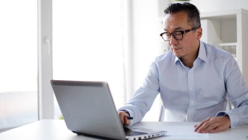 business, people, paperwork and technology concept - businessman with laptop computer and paper working in office