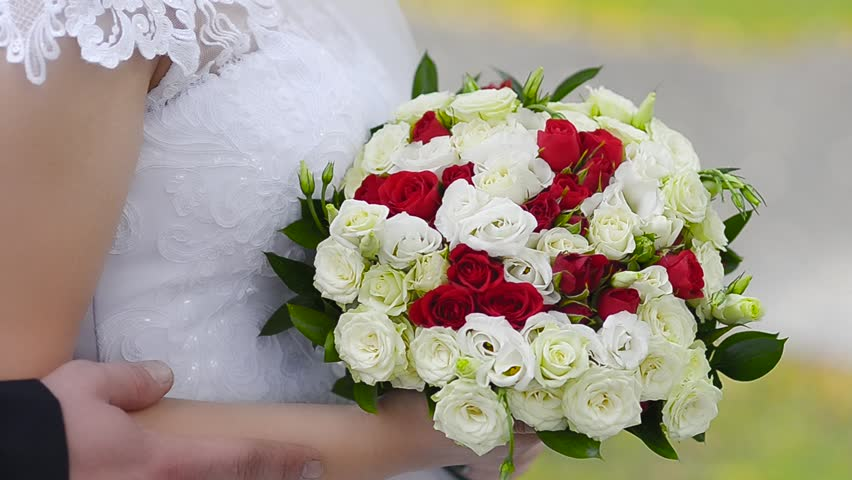 Bouquet of red and white roses in hands of the bride, a girl in a white dress standing with multicolored flowers in hands | Shutterstock HD Video #24032452
