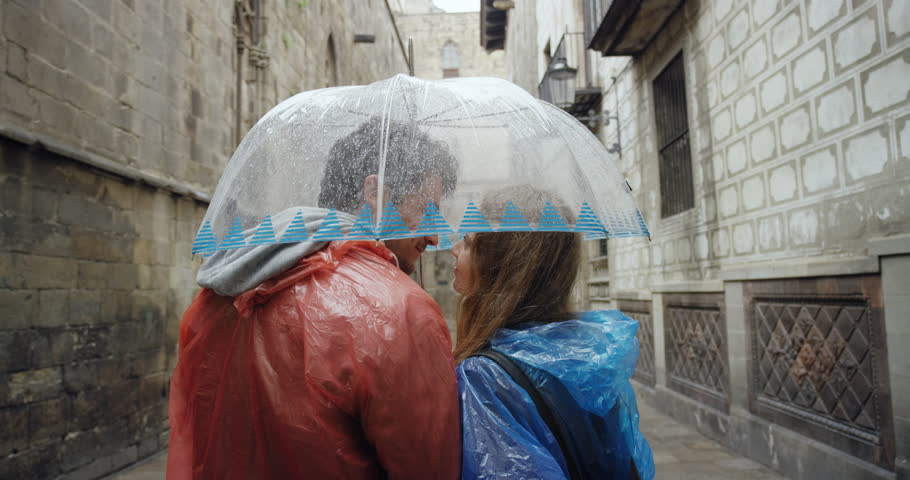 Tourist couple wearing brightly colored poncho in rainy European city kissing under umbrella sightseeing on vacation