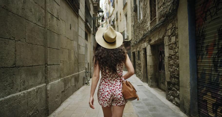 Rear view tourist woman Walking narrow streets of Barcelona Wearing cute summer dress enjoying European summer holiday travel vacation adventure | Shutterstock HD Video #24044134