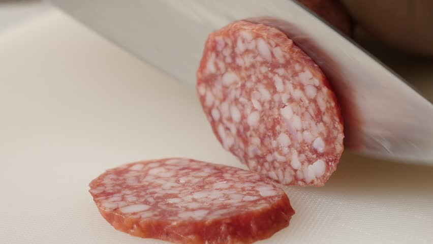 Close-up cutting cured sausage of air-dried meat 4K 2160p 30fps UltraHD footage - Salami cut on smaller pieces with knife 3840X2160 UHD video | Shutterstock HD Video #24044413
