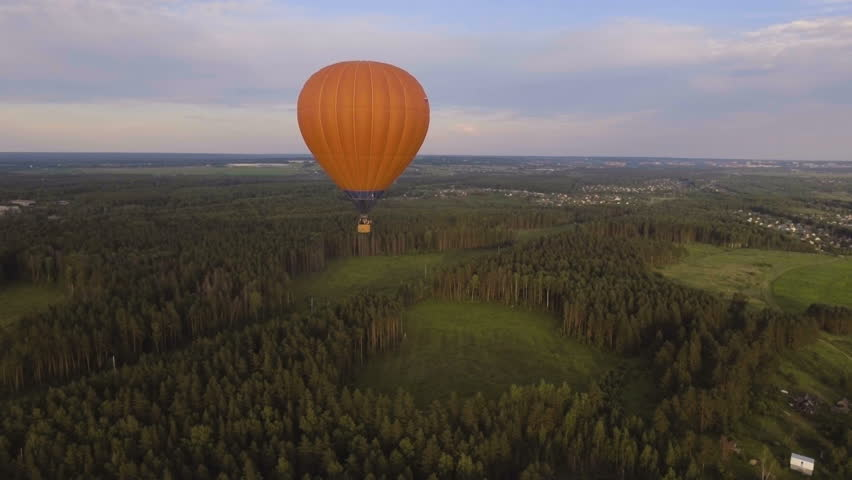 Aerial view:Hot air balloon in the sky over a field in the countryside in the beautiful sky and sunset.Aerostat fly on the countryside. 4K video,ultra HD.
