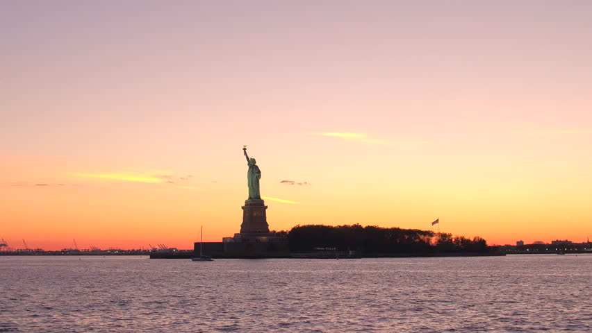 Iconic Lady Liberty - the Statue of Liberty National Monument on Liberty Island in New York Harbor against breathtaking golden sunset sky. Famous magnificent copper sculpture at dusk in New York City