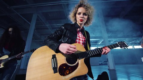Low angle camera quickly zooming in shooting rock band playing guitars with curly woman in leather jacket singing and two men standing on sides. Indoors, empty dark hall.