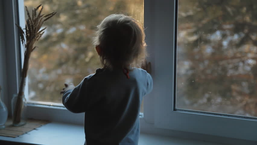 Small child standing at the window and enjoy the frosty morning | Shutterstock HD Video #24077743