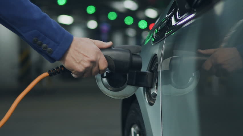 Senior is plugging in electric car at parking at vehicle charging stations. Close up. Slow motion 100 fps