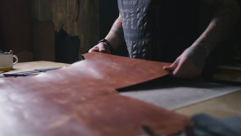 Craftsman work with big peace of leather at workshop, slow motion, close up