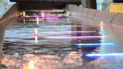 Ritual praying colorful candle floating on water for pray buddha at Wat Phra Non Chakkrasi Worawihan in Sing Buri , Thailand.